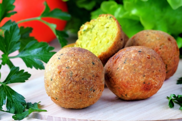 Falafel balls on a light cutting board. vegetarian and vegan middle eastern fastfood.