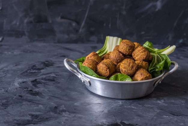 Falafel balls served in plate with green leafs on wooden black background