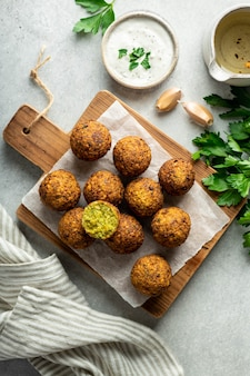 Falafel balls on a wooden cutting board, top view, selective focus
