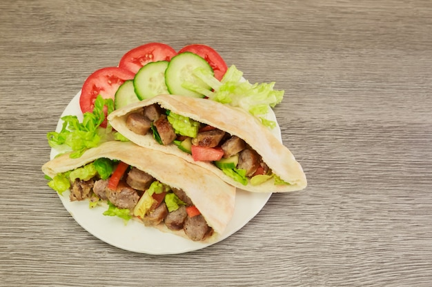 Falafel and fresh vegetables in pita bread on wooden