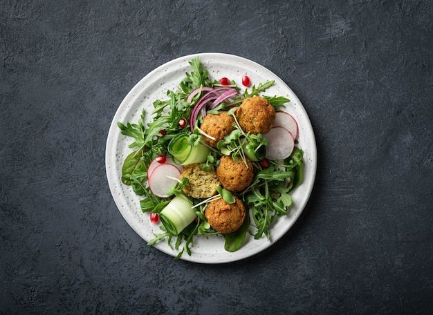 Falafel and fresh vegetables salad on a white ceramic plate on dark table, top view.