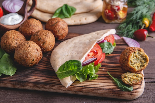 Falafel, fresh vegetables ,sauce and pita bread on wooden table