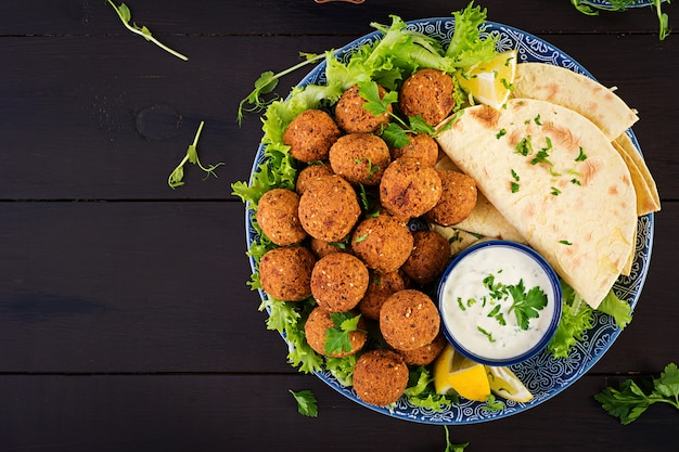 Falafel, hummus and pita. middle eastern or arabic dishes on a dark table halal food. top view. copy space