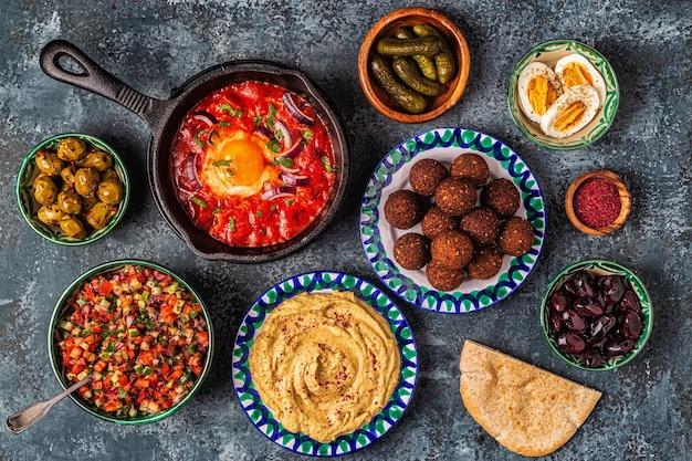Фалафель, хумус, шакшука, израильский салат - традиционные блюда израильской кухни. вид сверху.