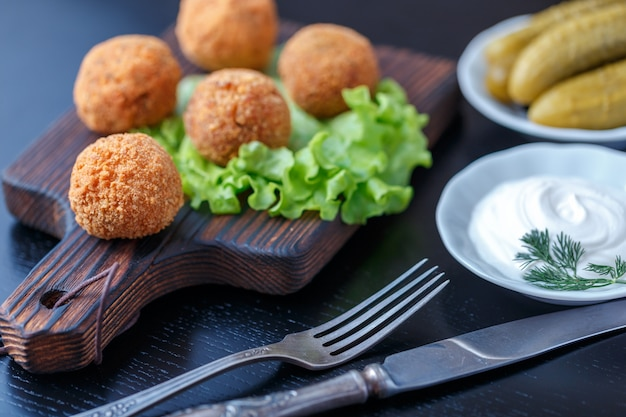 Falafel lies on a wooden cutting board.
