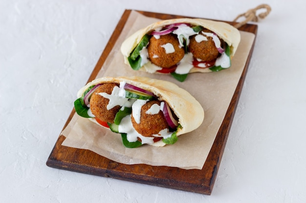 Falafel in pita with tomatoes, cucumbers, onions and spinach. healthy eating. vegetarian food.