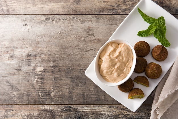 Falafel on a plate on wooden table, top view copyspace