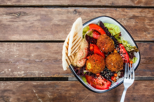 Falafel salad with hummus, beetroot and vegetables in bowl on wooden table, top view.