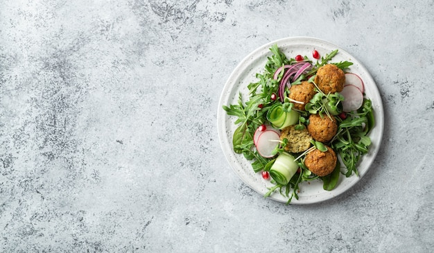Falafel and vegetables salad on a white ceramic plate on concrete table, top view, copy space