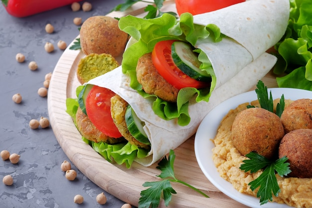 Falafel and vegetables wrapped in lavash and bowl with hummus on light cutting board.