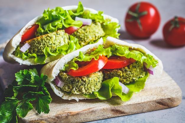 ボード上のピタパンに新鮮な野菜とファラフェル。健康的なビーガンフードのコンセプトです。