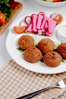 Falafel with fresh vegetables on table