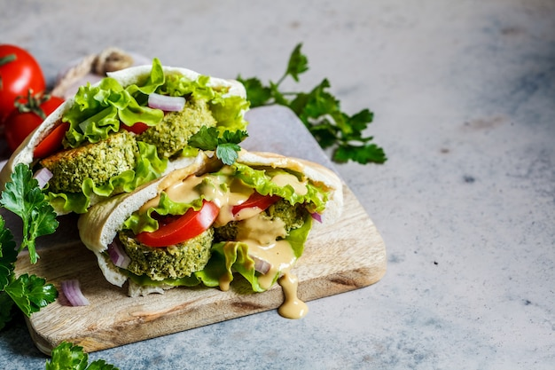 Falafel with fresh vegetables and tahini dressing in pita bread on the board. healthy vegan food concept.