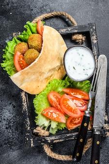 Falafel with vegetables, sauce in pita bread, vegetarian kebab sandwich.