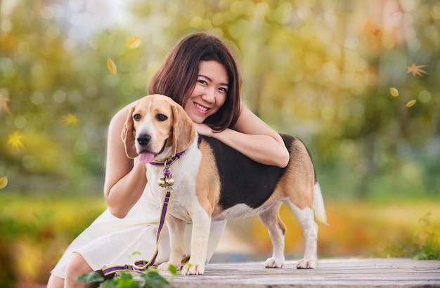 Осенний и осенний сезон. азиатская женщина вместе с собакой как лучший друг. открытый образ жизни в парке.