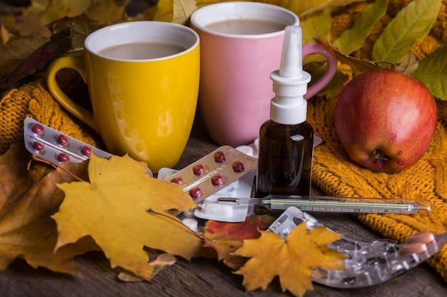 Падение и забота о здоровье. простуда и грипп. чашка чая, таблетки и термометр на деревянном фоне