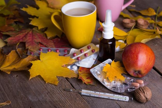Падение и забота о здоровье. чашка чая, таблетки и термометр на деревянном фоне