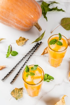 秋と冬の冷たいカクテル。白い大理石のテーブルの上の新鮮なミントとスパイシーなカボチャモヒート。コピースペース