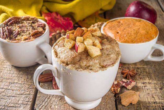 秋冬のスイーツ。伝統的な秋のケーキ、電子レンジのマグカップ-マグパンプキンパイ、アップルクランブルクリスプパイ、ピーカンマグケーキ