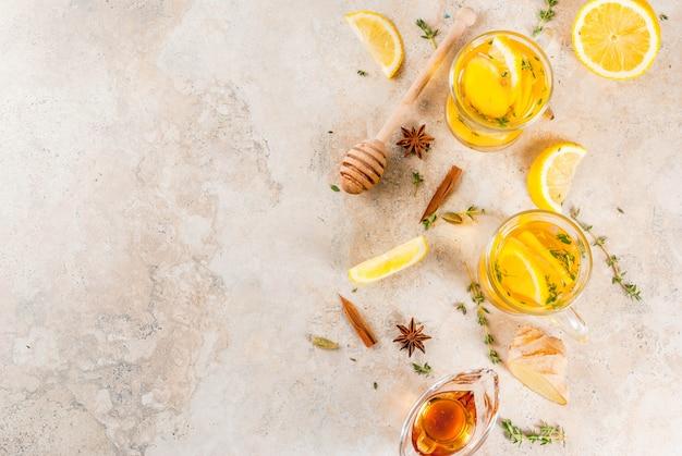 秋と冬の伝統的な飲み物。レモン、ジンジャー、スパイス(アニス、シナモン)とハーブ(タイム)の上面図と温かいお茶