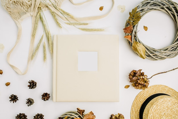 Fall autumn composition with wedding or family photo album, wreath frame, string bad, rye ears, cones, dry leaves, straw hat on white surface