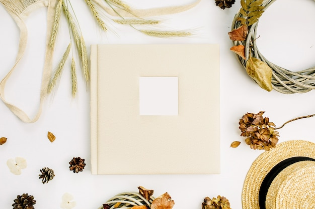 Fall autumn composition with wedding or family photo album, wreath frame, string bad, rye ears, cones, dry leaves on white surface