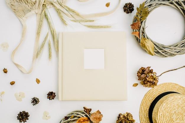 結婚式や家族の写真アルバム、花輪フレーム、ひも悪い、ライ麦の耳、コーン、乾燥した葉、白い表面に麦わら帽子と秋の秋の構成