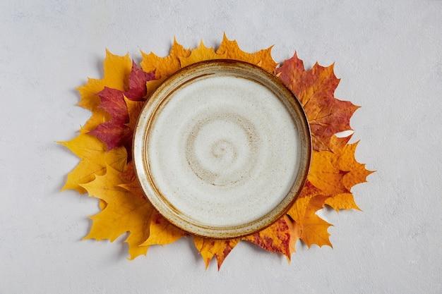 노란색 가을 단풍나무에 빈 흰색 판이 있는 가을 배경은 회색 콘크리트 배경 위에 있는 컴포지션 중앙에 흉내를 내며 놓여 있습니다.