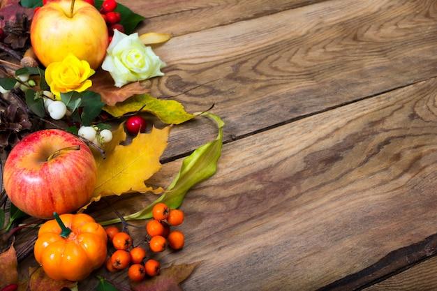 Fall background with pumpkin, apple, maple leaves, rowan,