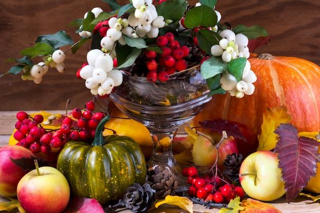 スノーベリーとナナカマドのアレンジメントと秋の背景