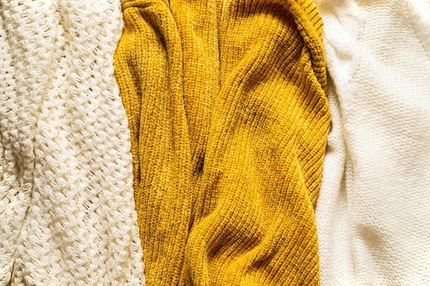 暖かいセーターで秋の背景。ニット服の山。秋冬のコンセプトです。