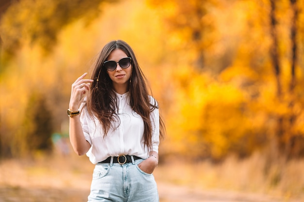 Fall concept - beautiful woman in autumn park under fall foliage
