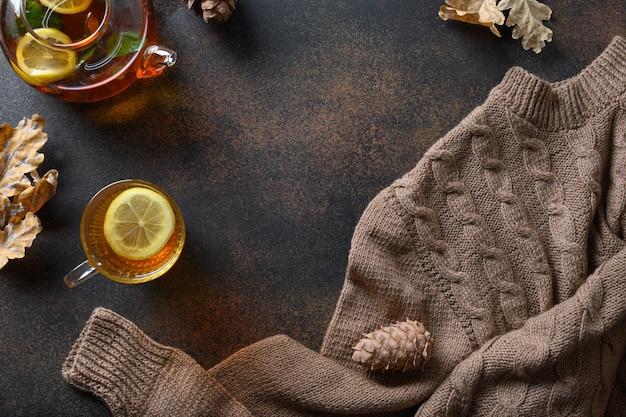 茶色の背景に温かいお茶、紅葉、セーターを備えた秋の居心地の良い構成。コピースペースを使用して上から表示します。