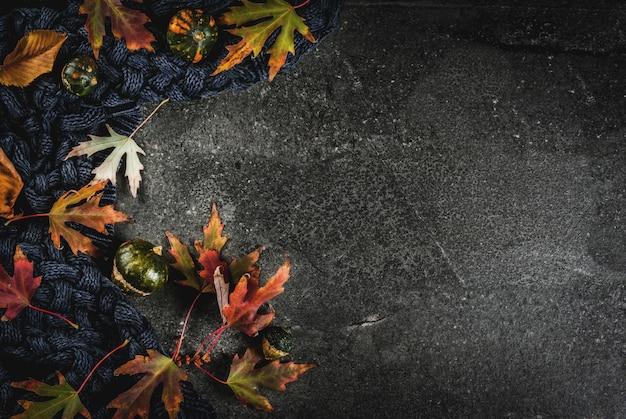 秋の赤と黄色の秋の暗い石の背景の葉暖かいセーターまたは毛布と小さなカボチャ、トップビューコピースペース