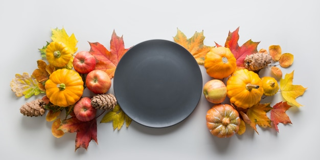 Fall decor for thanksgiving day with pumpkins, leaves, apples on grey