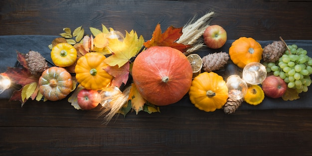 Fall decor for thanksgiving day with pumpkins, leaves, apples, lights on wooden table