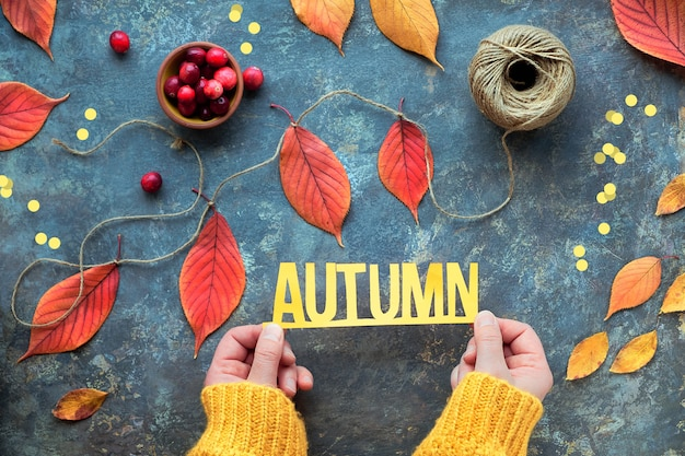 Fall decorations made at home with natural materials. paper text autumn in female hands.