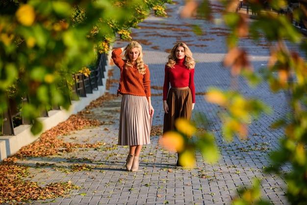 Осенняя мода. очаровательные дамы наслаждаются солнечным осенним днем. модная одежда. женственность и нежность. женщины, идущие в осеннем парке. юбка плиссе модная тенденция. друзья девушки. осенний стильный наряд.