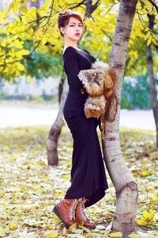 秋の晴れた日で都市公園でポーズをとって長いスタイリッシュなマキシドレスブーツを着て、毛皮の部分を保持しているセクシーな美しいアジアの女性の秋のファッションライフスタイルの肖像画。明るい色。