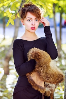 Ritratto di stile di vita di moda di caduta di bella donna asiatica sexy che indossa stivali lunghi eleganti maxi vestito e tenendo un pezzo di pelliccia, in posa al parco cittadino in una bella giornata di sole autunnale. colori luminosi.