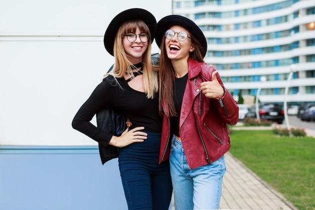 秋のファッションルック。ビジネスセンターでポーズかわいい丸いメガネと黒い帽子で魅力的な優雅な女の子のカップル。