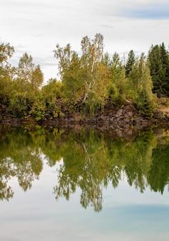 Падение листвы отражается на озере с зеркальной поверхностью воды.