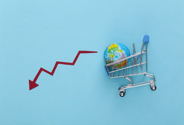 The fall of global shopping. supermarket trolley with a globe, falling arrow tending down on a blue.