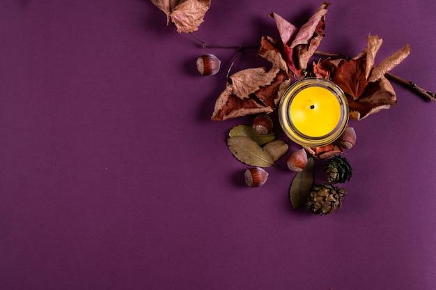 色の背景に上から金色の葉とキャンドルを落とします。テキスト用のスペースをコピーします。平らに秋。秋のフラットレイ。紅葉とナッツ。