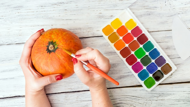 Fall halloween crafts. female hands with orange decorative pumpkin and bright paint