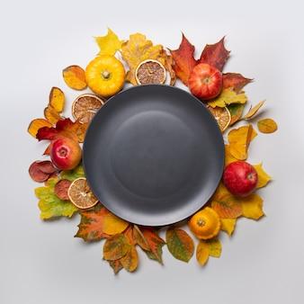 リンゴと色鮮やかな葉の秋の収穫とスペースのある中央の黒い皿。上面図。