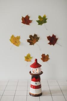Осеннее украшение дома со свечой в подсвечнике сушеные листья на белом фоне