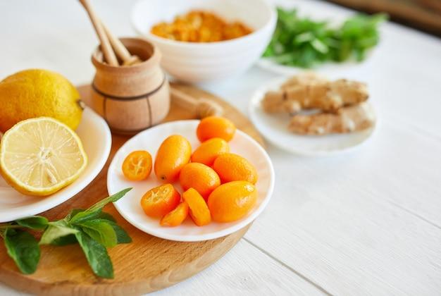 秋の免疫システムはビタミンの健康を高めます。新鮮なキンカン、シーバックソーン、生姜、レモン、蜂蜜、柑橘類、ミントの上面図