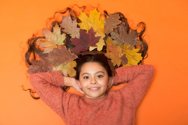 Fall is on her mind. girl cute kid lay on orange background with fallen leaves. child enjoy fall season. dry maple leaves in her hairstyle. fall season concept. hair care in autumn tips and ideas.