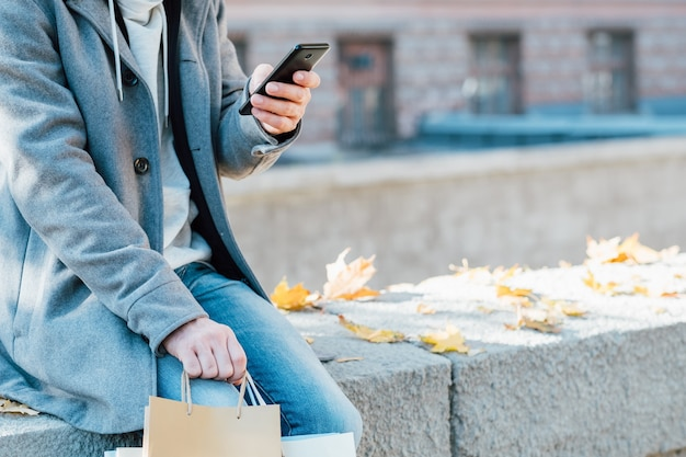 Fall melancholy. cropped shot of man sitting alone on wall with shopping bags, using smartphone.